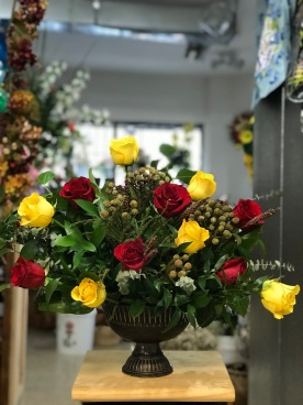 25.) Red and Yellow Roses with a rustic bronze vase.